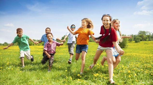 Eine Gruppe Kinder rennt über eine Wiese.