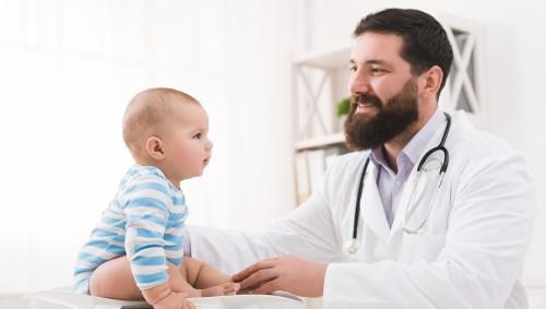 Ein Kinderarzt wiegt ein Baby.