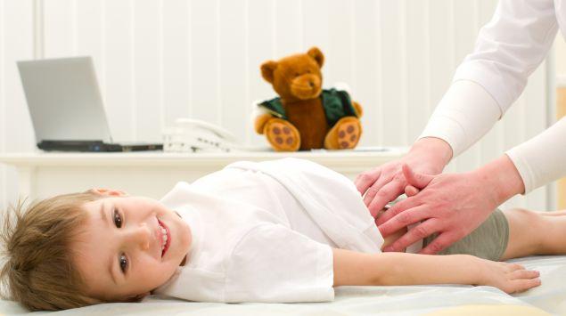 Ein Kinderarzt tastet die Beckenregion eines Jungen ab.