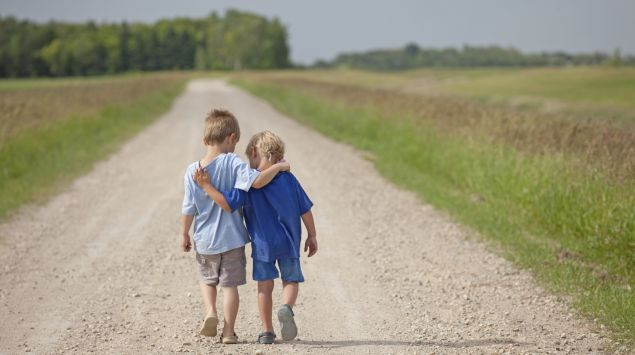 Man sieht zwei Jungen von hinten, die Arm in Arm gehen.