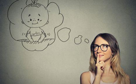 Eine junge Frau denkt darüber nach, ein Baby zu haben (symbolisiert durch eine Denkblase).
