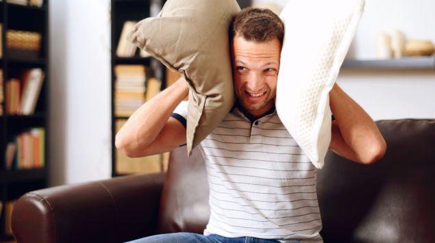 Das Bild zeigt einen Mann, der sich die Ohren mit zwei Kissen zuhält.