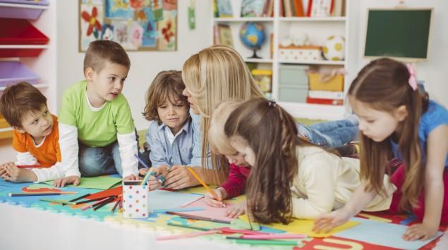 Eine junge Erzieherin sitzt in einer Kindertagesstätte mit drei Jungen und drei Mädchen an einem Tisch mit Zeichenutensilien.