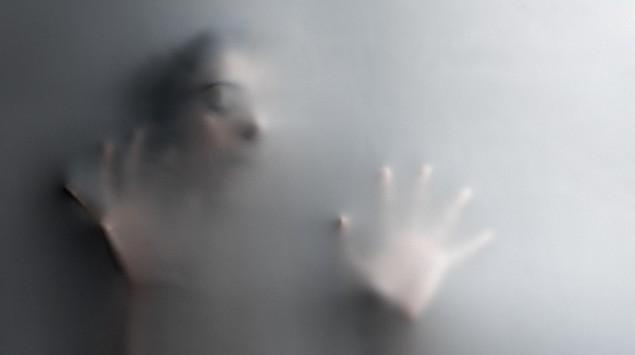 Mensch hinter beweglicher Wand, von Angst erfüllt