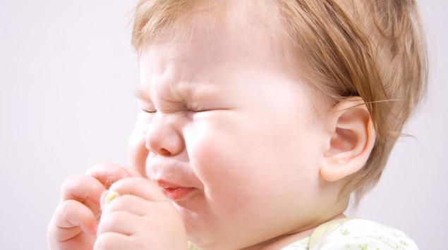 Das Bild zeigt ein niesendes Kleinkind.