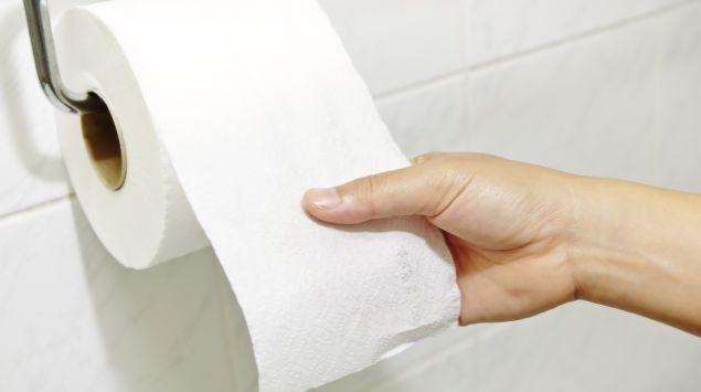 Jemand reißt Toilettenpapier von einer Rolle ab.