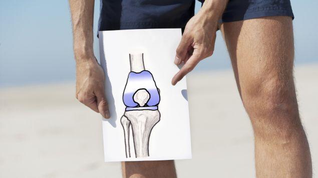 Das Bild zeigt einen Mann, der ein Blatt mit einem aufgemalten Knie in der Hand hält.