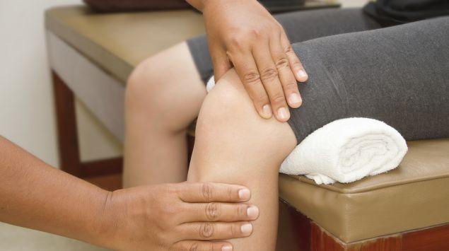 Ein Arzt untersucht das Knie eines Patienten.