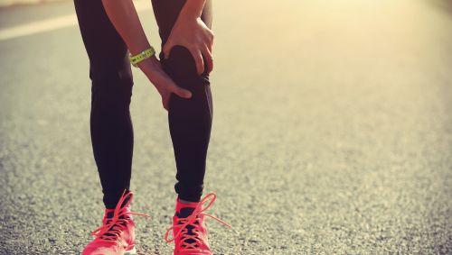 Das Bild zeigt eine Joggerin, die vor Schmerzen ihr Kniegelenk hält.