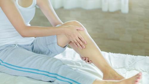 Eine Frau hält sich das schmerzende Knie.