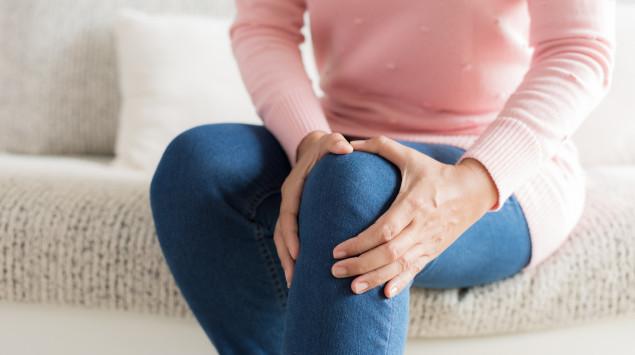 Eine Frau umfasst ihr schmerzendes Knie. Treten Gelenkschmerzen bei oder nach einem bakteriellen Infekt auf, kann es sich um eine reaktive Arthritis handeln.