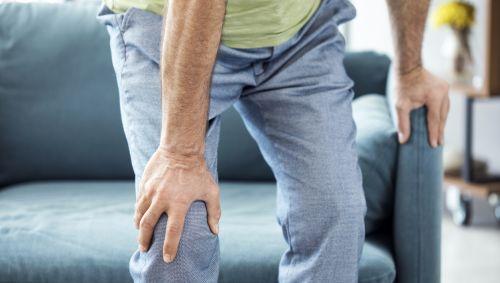 Ein älterer Mann stützt sich auf die Sofalehne und fasst sich ans schmerzende Knie.