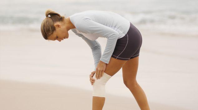 Das Bild zeigt eine Frau in Laufbekleidung, die unter Knieschmerzen leidet.