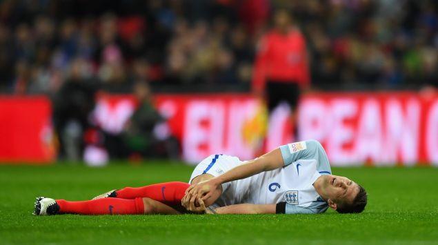 Das Bild zeigt einen Fußballer, der auf dem Rasen liegt und sein Knie hält.