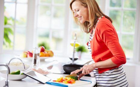 Clean Eating: Eine Frau kocht und blickt auf ein Tablet.