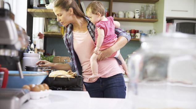 Eine junge Frau hält ein Baby auf dem linken Arm, während sie mit der rechten Hand in einem Kochtopf rührt.