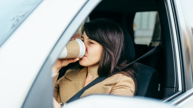 Eine Frau am Steuer eines Autos trinkt Kaffee aus einem Becher.
