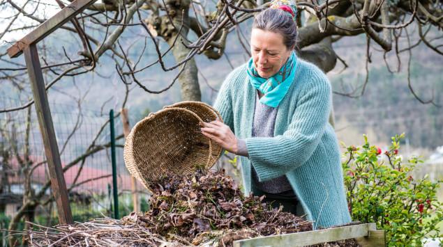 Eine Frau schüttet etwas auf den Kompost. Im Kompost können sich Schimmelpilze wie Aspergillus aufhalten