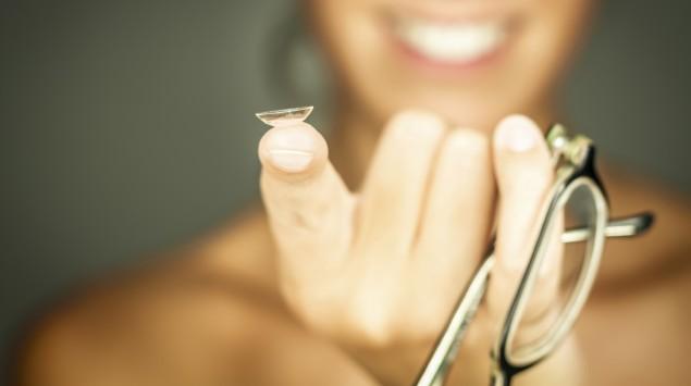 Eine lachende Frau hält eine Brille und eine Kontaktlinse in der Hand.
