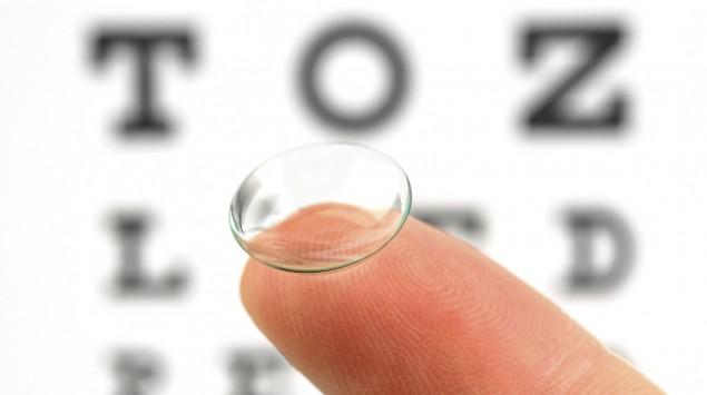 Eine Kontaktlinse liegt auf einer Fingerspitze, im Hintergrund ist eine Sehtesttafel zu sehen.