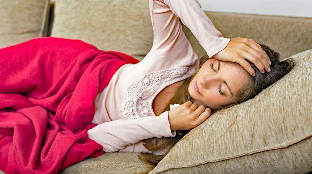 Das Bild zeigt eine junge Frau, die mit Kopf- und Gliederschmerzen auf dem Sofa liegt.