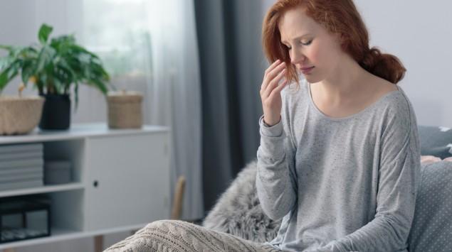Eine Frau sitzt auf einem Sofa und greift sich an den Kopf.