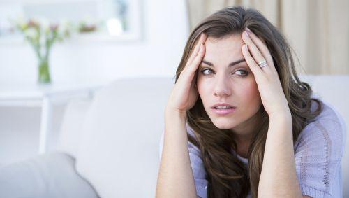 Das Bild zeigt eine junge Frau mit Kopfschmerzen.