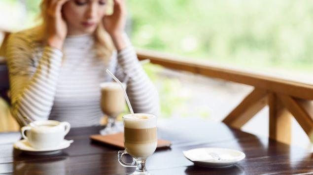 Das Bild zeigt eine blonde Frau, die im Cafe sitzt und Kopfschmerzen hat.