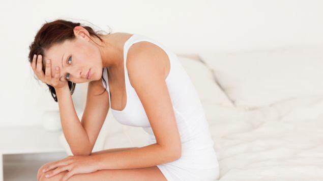 Eine Frau sitzt auf der Bettkannte und stützt den Kopf in die Hand.