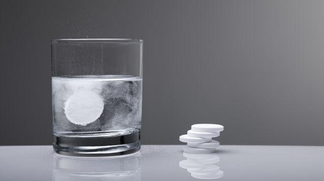 Kopfschmerztablette löst sich in Wasserglas auf
