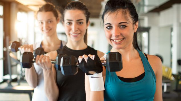 Drei junge Frauen trainieren im Fitnessstudio mit Hanteln