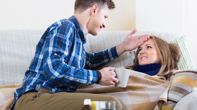 Eine Frau liegt krank auf dem Sofa, ihr Freund kümmert sich um sie.