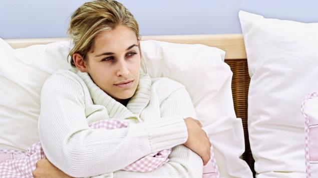 Das Bild zeigt eine kranke Frau im Bett.