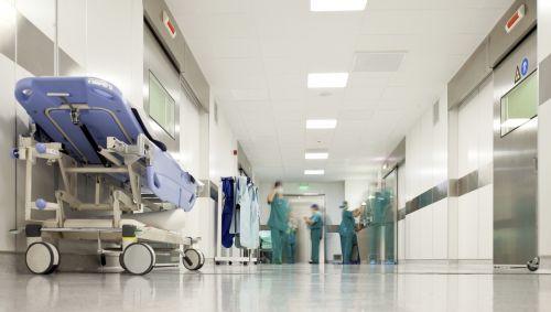 Das Bild zeigt einen Krankenhausflur mit einem Bett und Personal.