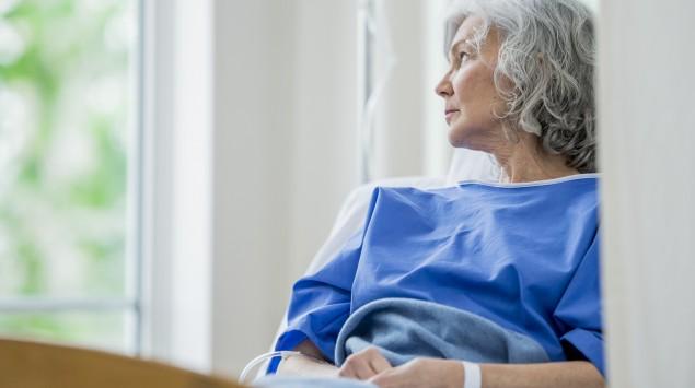 Man sieht eine ältere Frau in einem Krankenhausbett.