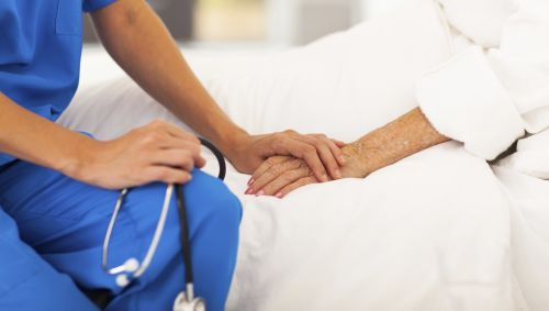Ein Pfleger sitzt am Bett einer Patientin.
