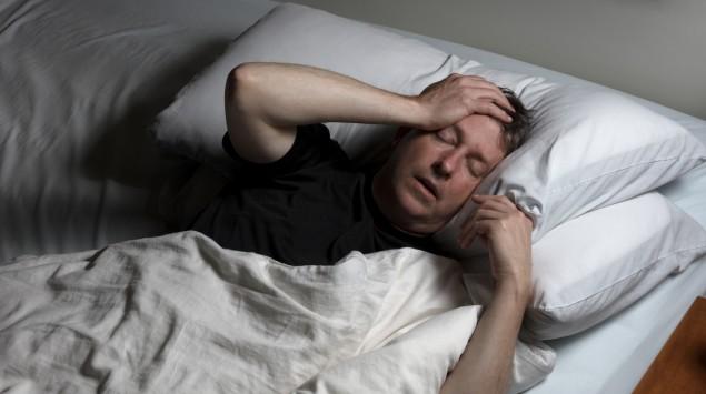 Ein Mann liegt im Bett und fasst sich mit Leidensmiene an den Kopf.
