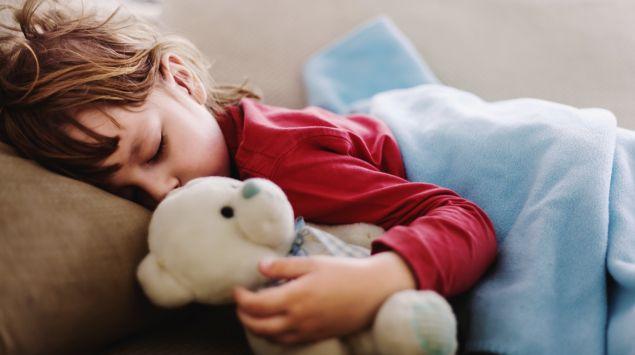 Ein Kind mit Norovirus-Infektion schläft erschöpft auf dem Sofa und hält einen Teddybär im Arm.