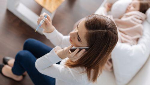 Eine Frau sitzt neben einem kranken Kind auf dem Sofa, hält ein Fieberthermometer in der Hand und telefoniert.