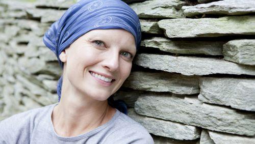 Das Bild zeigt eine krebskranke Frau mit einem Kopftuch auf dem Kopf.