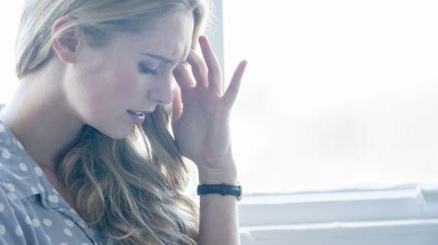 Das Bild zeigt eine junge Frau von einem Fenster, die ihre Hand an ihre Stirn hält.