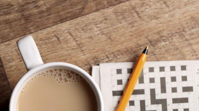 Das Bild zeigt einen Tischplatte, auf der ein Kaffee und ein Kreuzworträtsel liegt.