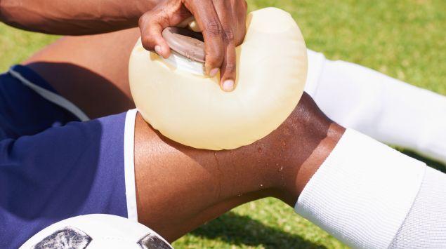 Ein Fußballer kühlt sein verletztes Knie.