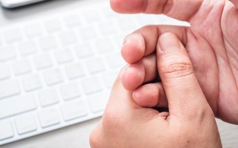 Kribbeln in den Händen: Jemand hält Finger der rechten Hand mit der linken Hand umfasst, im Hintergrund sieht man eine Computer-Tastatur.