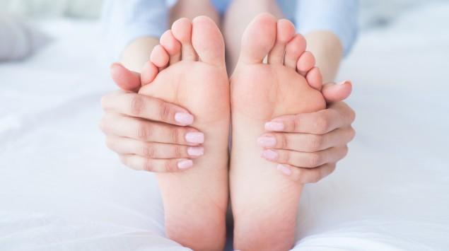 Kribbeln: Eine Frau umfasst ihre Füße mit den Händen.