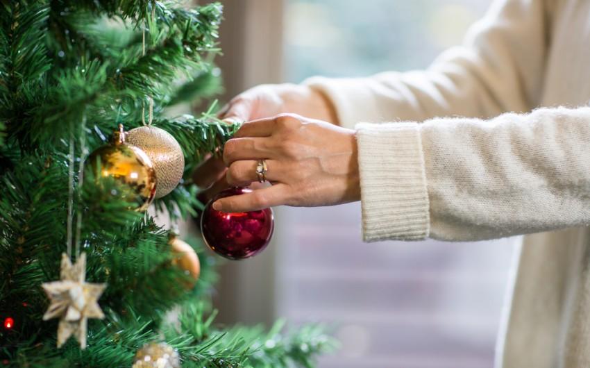Eine Frau schmückt einen künstlichen Weihnachtsbaum.