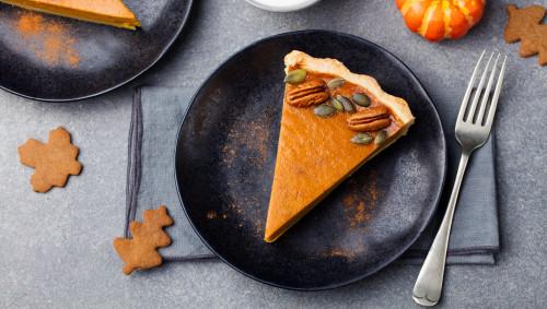 Ein Stück Kürbiskuchen mit Nüssen auf einem Teller.