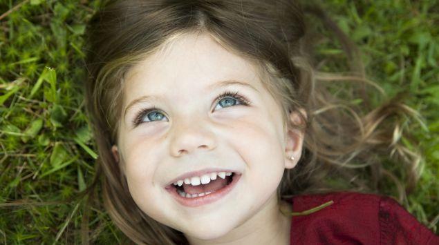 Das Bild zeigt ein lachendes Kind, das auf dem Rasen liegt.