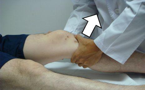 Das Bild zeigt einen Arzt, der die Kniestabilität eines Patienten testet.
