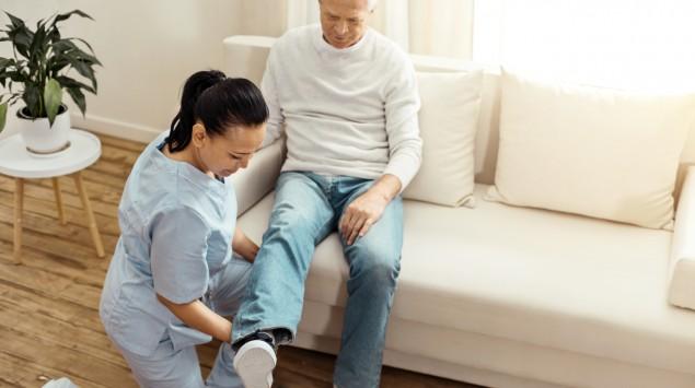 Eine Physiotherapeutin behandelt einen älteren Mann.